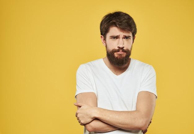 白いtシャツを着た男性が、黄色の背景のトリミングされたビューを手でジェスチャーします。
