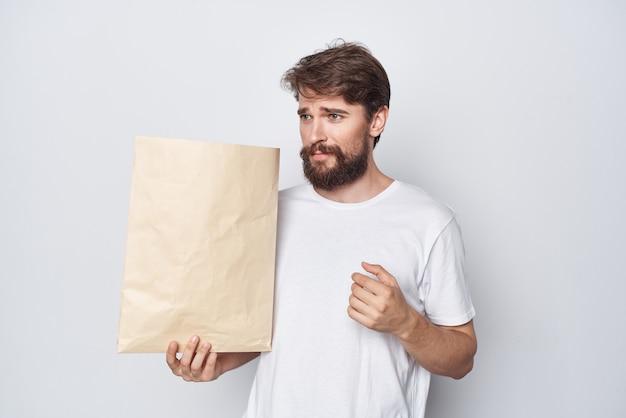 明るい背景に彼の手で紙袋を持つ白いtシャツの男