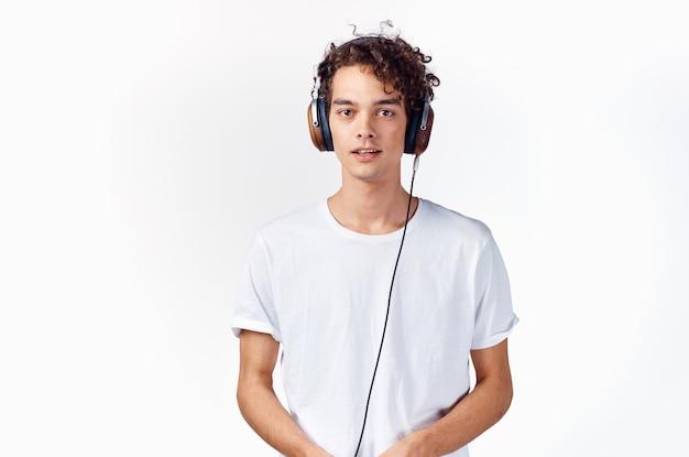 ヘッドフォンを付けた白いtシャツを着た男性が、音楽の感情の喜びの楽しみを聞く