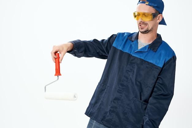 Мужчина в рабочей форме валик для покраски стен в его руках украшение ремонт