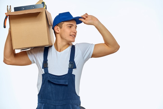 手に箱を持って配達サービスを積んでいる作業服を着た男性
