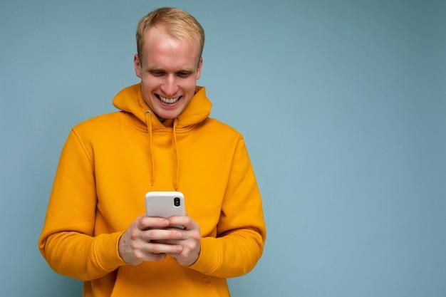 Мужчина в желтой кофте с мобильным телефоном.