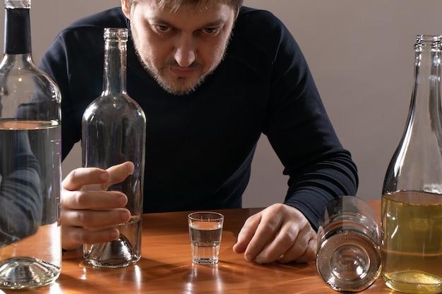 アルコール中毒の男性がコップ一杯のアルコールを持っています。アルコール依存症、中毒、せん妄