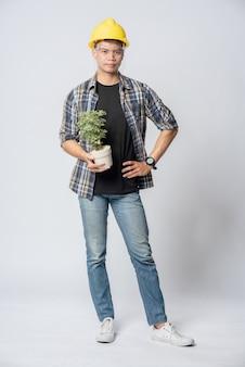 Человек в инженерной шляпе и стоял, держа горшок с растением в своем доме.
