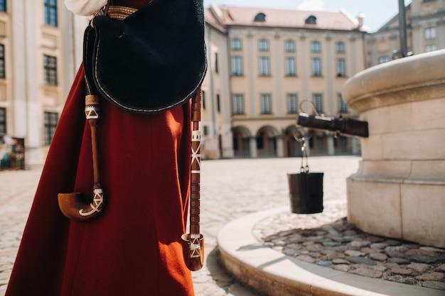 ネスヴィシ城の広場にある古い赤いドレスのクローズアップの男。ベラルーシのネスヴィシ城。