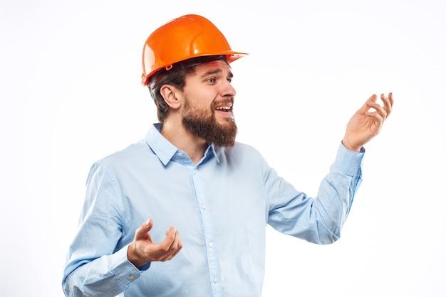 Мужчина в оранжевой рубашке шлема строительной индустрии