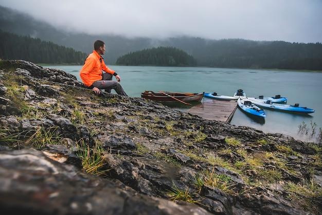 オレンジ色のジャケットを着た男が雨と曇りの天気でモンテネグロの黒い湖のそばに座っています