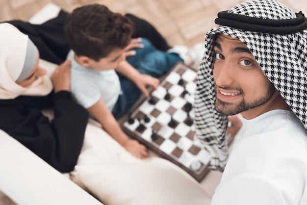 Мужчина в арабской одежде играет в шахматы с маленьким мальчиком.
