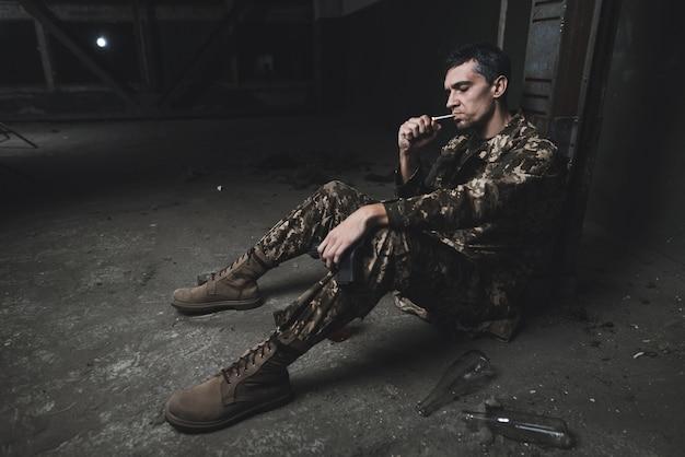 Человек в военной форме сидит и думает о чем-то.