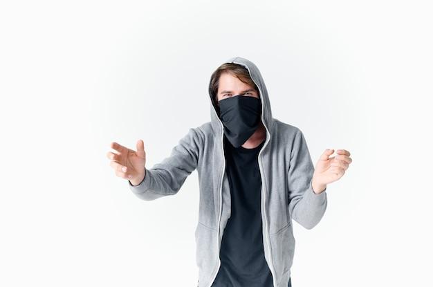 Мужчина в балаклаве с капюшоном анонимность преступление светлый фон