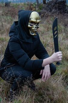 Человек в черной одежде сидит на корточках с огромным ножом мачете.