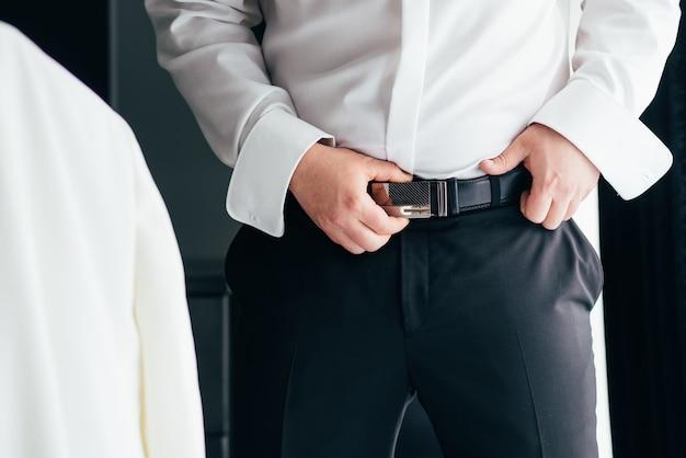 Мужчина в черных брюках и белой рубашке застегнул коричневый кожаный брючный ремень.