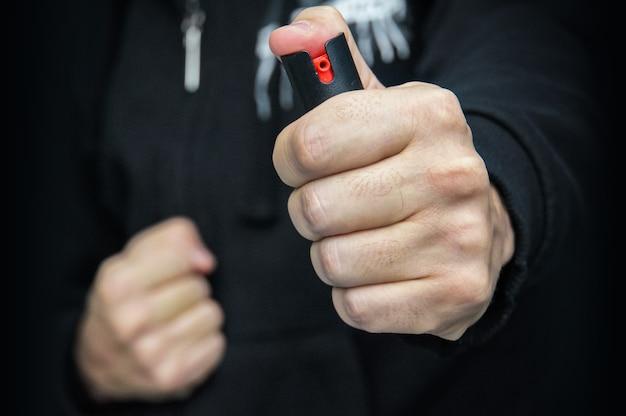 黒い制服を着た男性が催涙ガスまたは唐辛子スプレーを手袋をはめています。自己防衛の手段。ガスカートリッジ、ガスボンベ