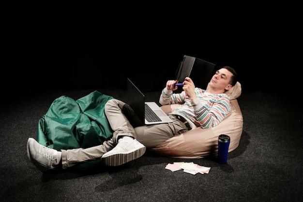밝은 옷을 입은 남자가 푸프에 누워 무릎에 노트북을 들고 글라이더를 들여다 본다.