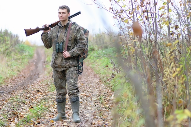 봄 사냥에 숲 벨트에 위장과 총을 가진 남자