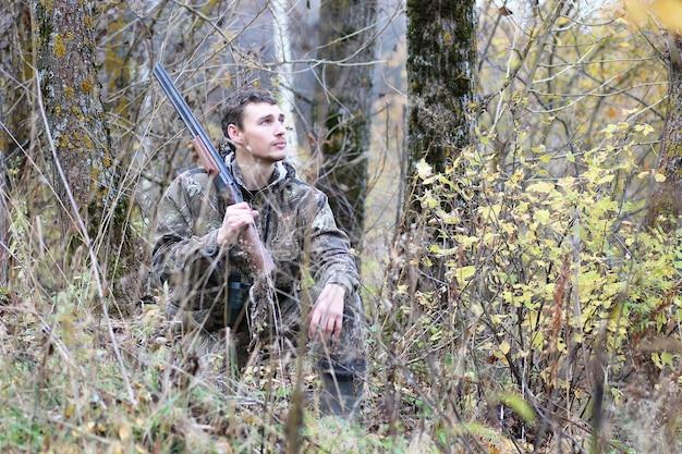 Мужчина в камуфляже и с ружьями в лесополосе на весенней охоте