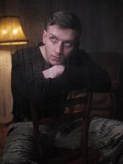 迷彩パンツの男が雨の窓のそばに座っている
