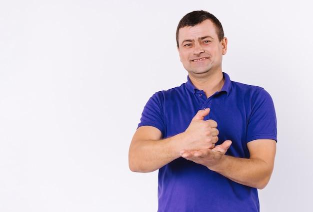캐주얼 한 옷을 입은 남자가 카메라를보고 미소 짓습니다. 청각 장애인 남자 수화 표시