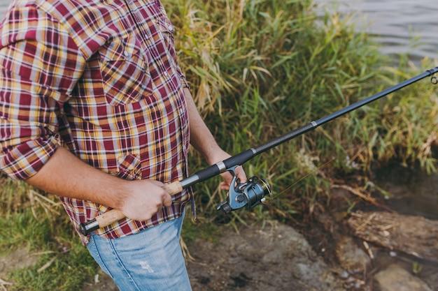 소매가 걷힌 체크 무늬 셔츠를 입은 남자가 낚싯대를 들고 관목과 갈대 근처의 호숫가에서 릴을 풀고 있습니다. 라이프 스타일, 레크리에이션, 레저 개념입니다.