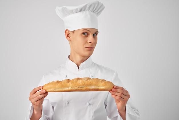 Мужчина в одежде поваров с багетом в руках ресторанов для гурманов