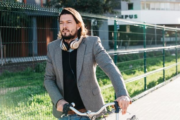 Мужчина в суде с наушниками на шее гуляет с велосипедом на улице
