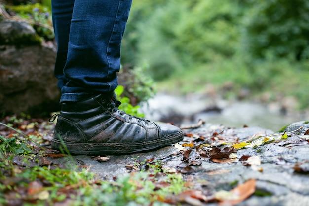 Человек в грязных туфлях осенью стоит