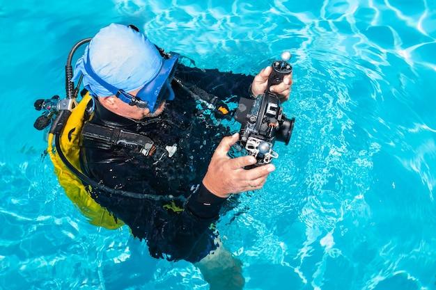 カメラを持っているダイビングスーツの男