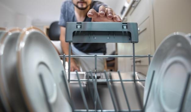 개방형 식기 세척기 앞에 있는 남자가 씻은 후 깨끗한 접시를 꺼냅니다.