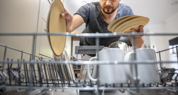 열린 식기세척기 앞에 있는 남자가 접시를 꺼내거나 내려놓는다.