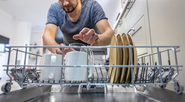 開いた食器洗い機の前にいる男性が、皿を出し入れします。