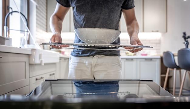 Мужчина перед открытой посудомоечной машиной с тарелкой.