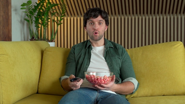 スポーツゲームや映画を見ながら、黄色いソファに座ってポップコーンを食べているテレビの前の男