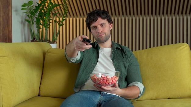 Мужчина перед телевизором смотрит спортивный матч или фильм, сидит на желтом диване и ест попкорн