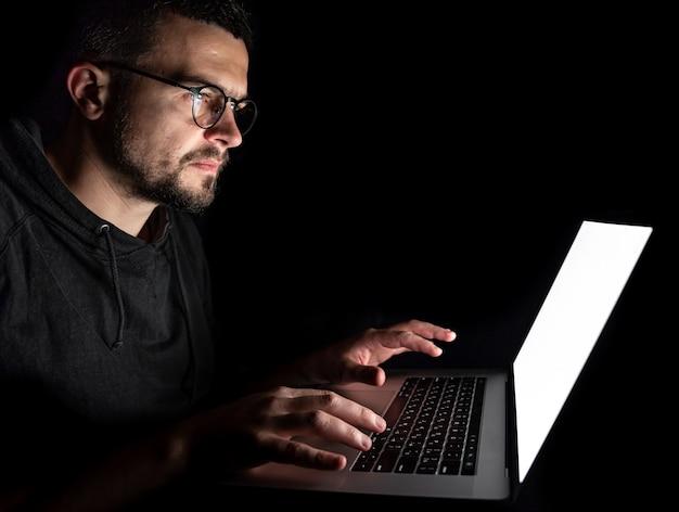 眼鏡をかけた男性は、ノートパソコンの画面を真剣に見て、暗闇の中で夜にコンピューターで働いています。
