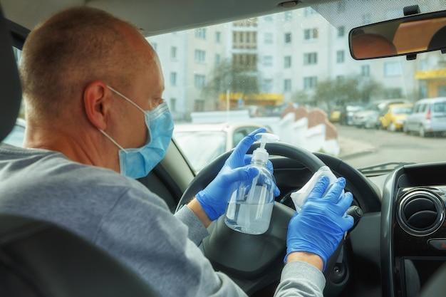 手袋とマスクをした男性が消毒用ワイプでハンドルを拭く