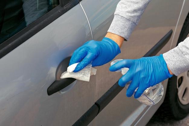 장갑을 낀 남자가 소독제로 차 문을 닦는다.