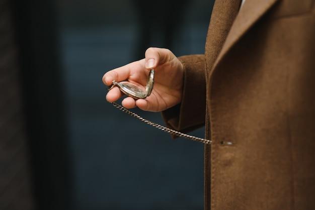 Мужчина в сером деловом костюме держит золотые карманные часы.