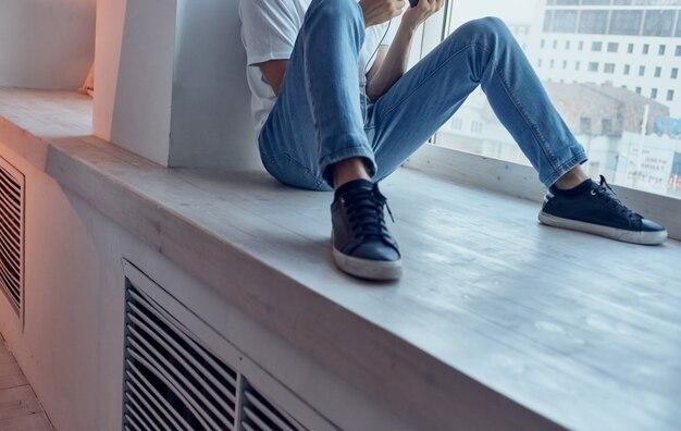 Мужчина в наушниках на подоконнике у окна слушает музыку