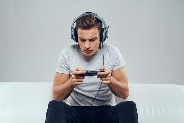 헤드폰을 쓴 남자가 소파 모바일 게임 콘솔 취미 엔터테인먼트에 앉아 있습니다. 고품질 사진