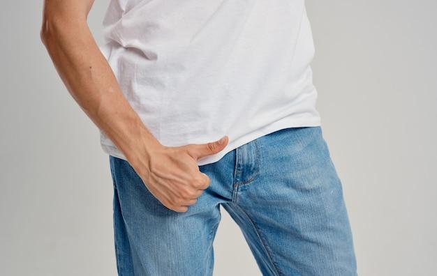 ジーンズとtシャツを着た男性がベルトの下に親指を立てている