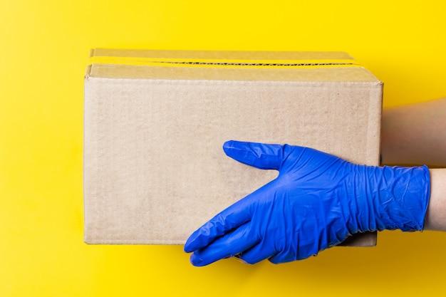 ラテックス手袋をした男性が小包を配達します。コロナウイルスのパンデミック時の商品の安全な配達の概念。