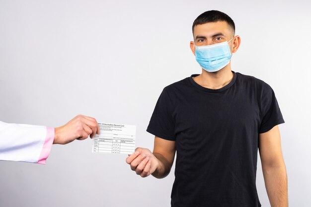 Мужчина в медицинской маске получает карту вакцинации от врача