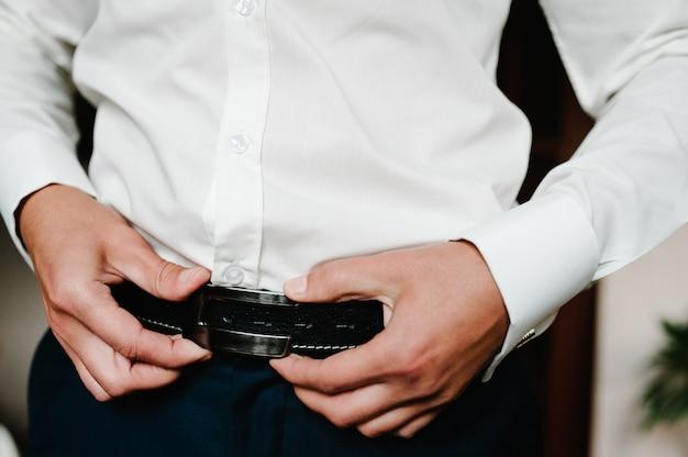 Мужчина в брюках и рубашке застегнул черный кожаный брючный ремень. жених нарядите ремень с пряжкой. бизнесмен носить кожаный стильный пояс. новый классический ремень.