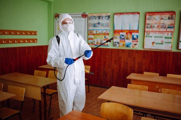 항균 보호복을 입은 남자가 소독액이 든 스프레이로 교실을 청소하고 있습니다. 전문 위생 작업자가 특수 장비로 강당을 소독합니다. 의료 개념입니다.