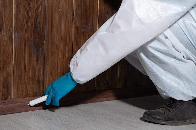 Мужчина в защитной одежде обеззараживает дом от домашних вредителей и насекомых.