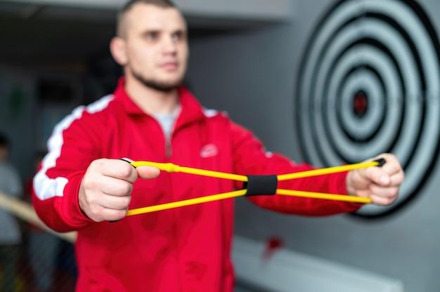赤いジャケットを着た男性がジムで手の運動器具を使って練習しています