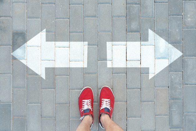 빨간 운동화를 입은 남자가 방향 표시기 앞에서 멈췄다. 의사 결정 개념.