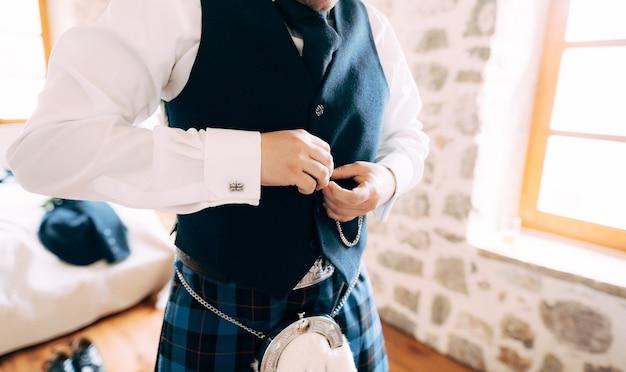 スコットランドの民族衣装を着た男性がチョッキをボタンで留め、結婚式の準備をします