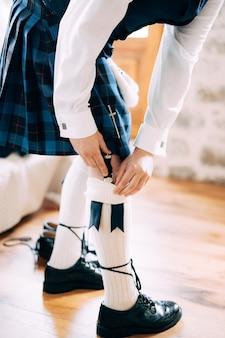 スコットランドの民族衣装を着た男性がホテルの部屋で結婚式の準備をする