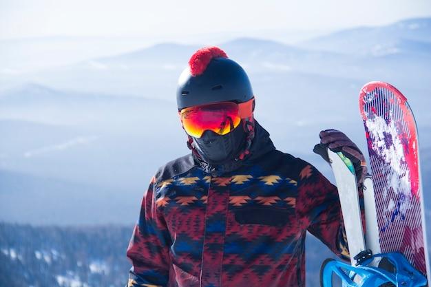 산 꼭대기에서 스노보드 장비를 입은 남자